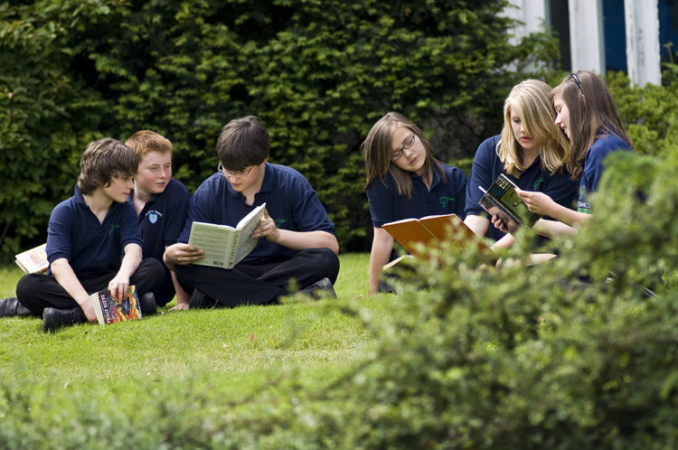 Students reading books on the grass in the grounds.